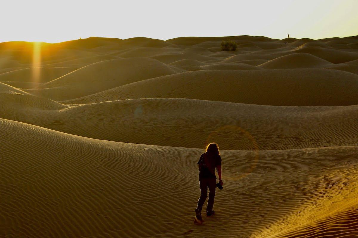Photographer climbing sand dunes